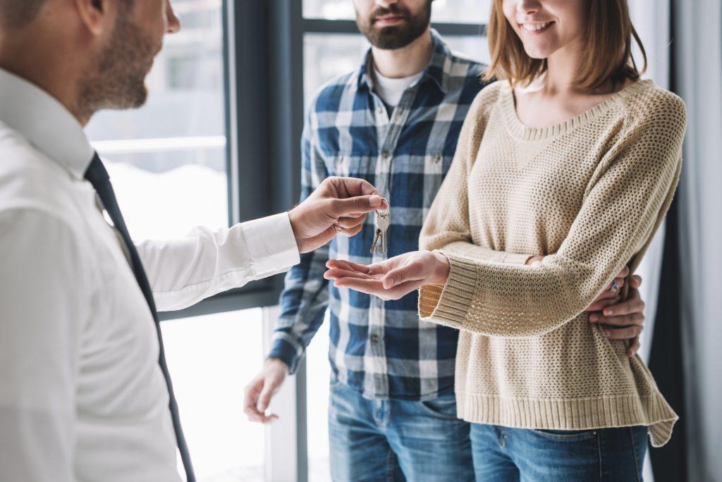 crop couple taking keys from real estate agent Tudo que você precisa saber sobre investir em imóveis em 2021